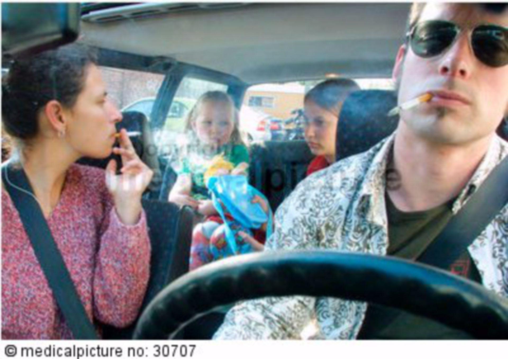 Rauchende Eltern mit Kindern im Auto