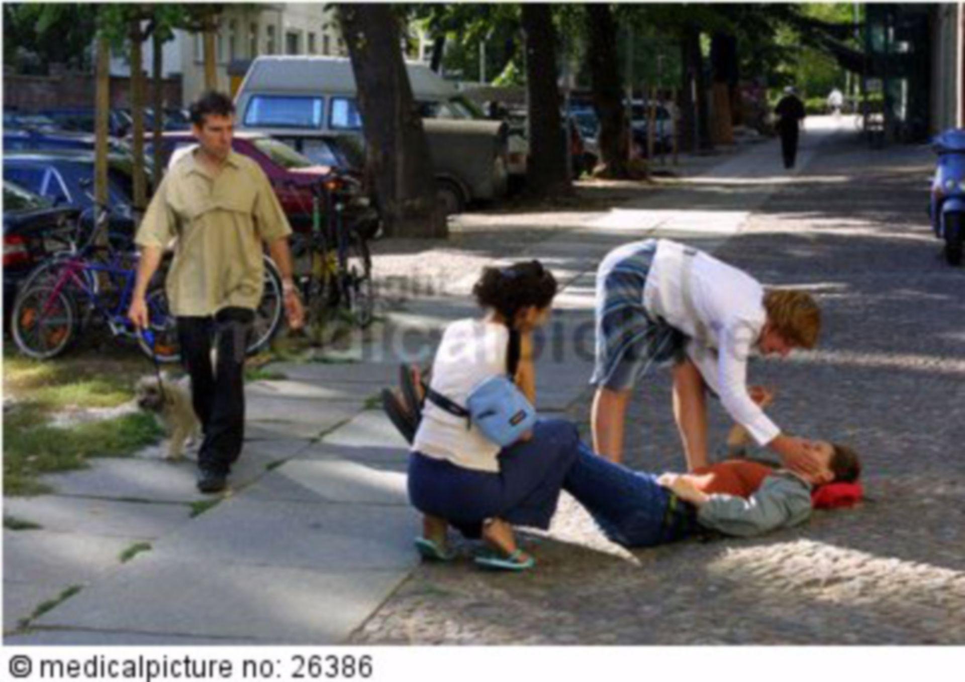 Ohnmächtige Person auf Straße mit Ersthelfern