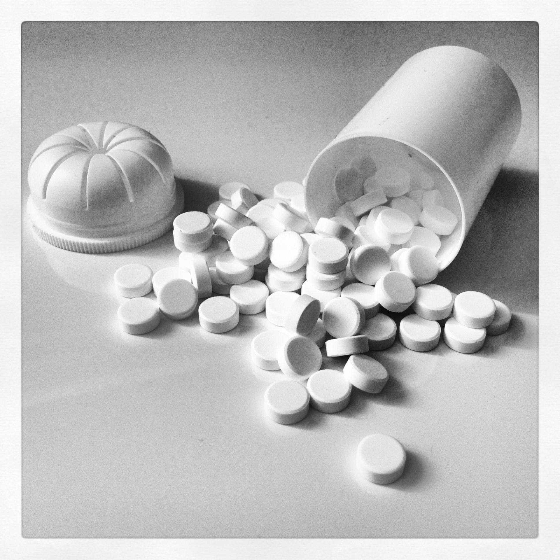 Pills in front of pill bottle