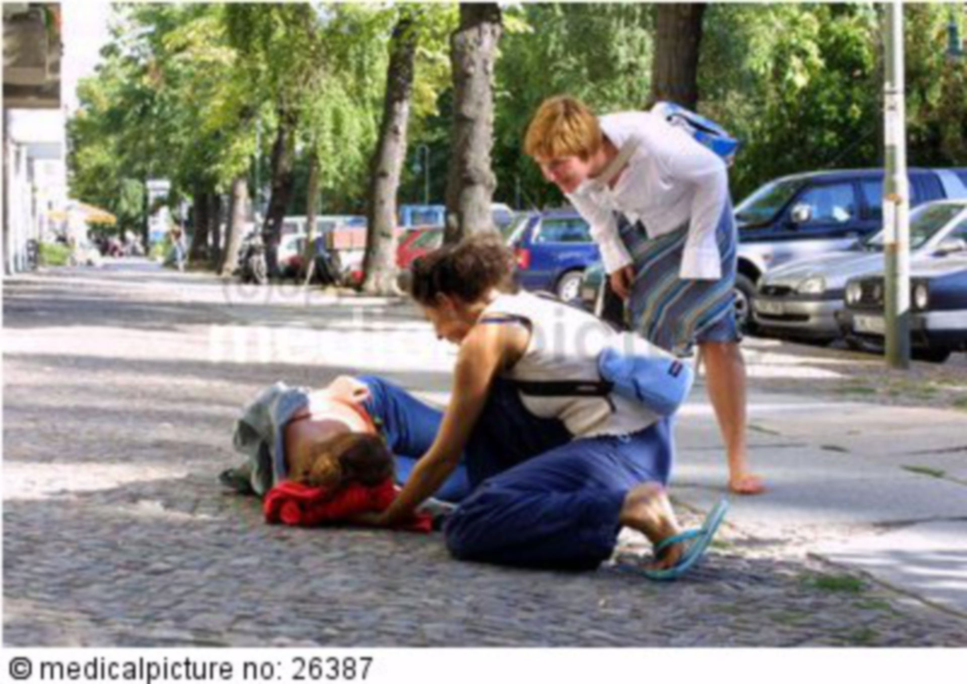 Unconscious person on the street with first responders