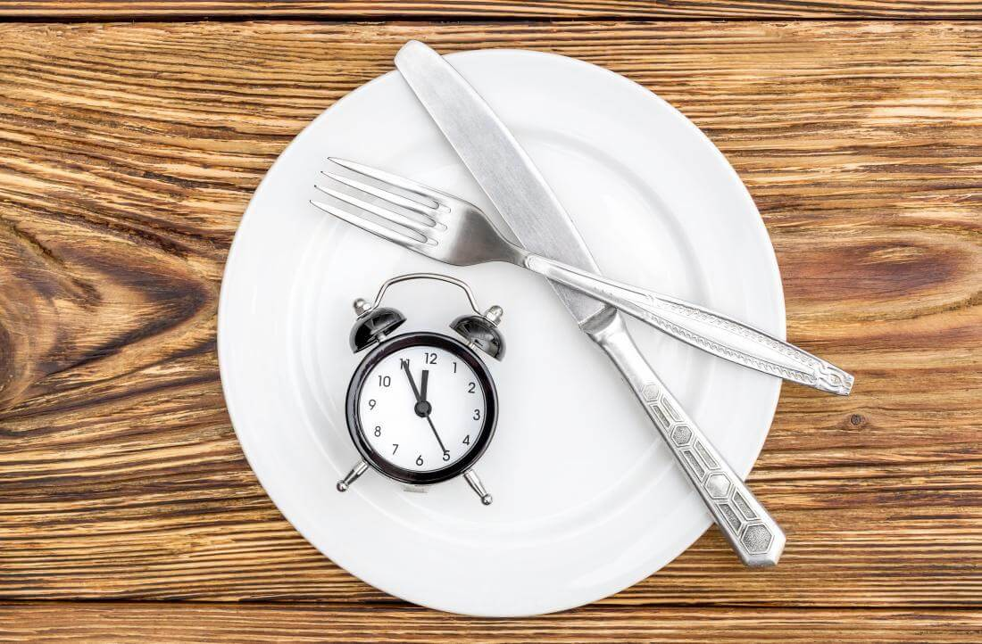 empty-plate-on-wooden-table-with-knife-and-fork-and-alarm-clock_original.jpg